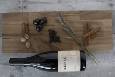 A table with a bottle of Skinner red wine, cinnamon sticks, nuts and berries