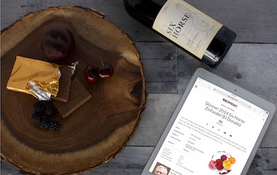 A bottle of red wine next to a tablet and a piece of chocolate and berries