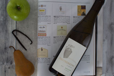 A bottle of wine with a green apple and a pear next to it