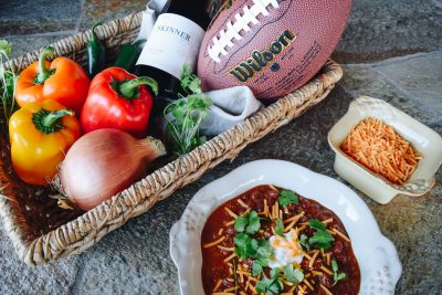 Basket with bell peppers, onion, an american football and a bottle of Skinner red wine