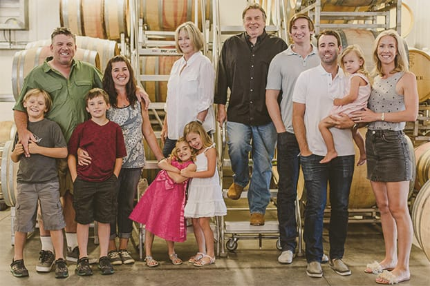 The Skinner family portrait standing in front of the wine barrels