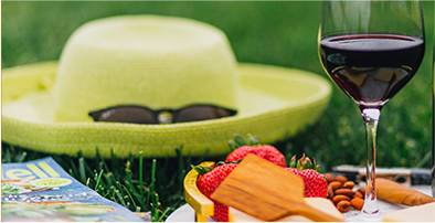 Picnic in a park with a glass of red wine, a summer yellow hat and strawberries